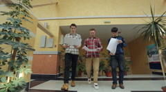 Men dressed in checkered shirts walk through shopping mall Stock Footage