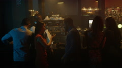 4K Young diverse group socializing & bar staff serving drinks in trendy city bar - stock footage