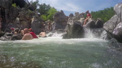 Kid falling over backwards on water fall Stock Footage