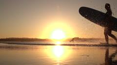 SLOW MOTION: Smiling surfer girl running out of ocean splashing water at sunset Stock Footage