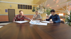 Handsome men sit at round wooden table and discuss plan of buiding Stock Footage