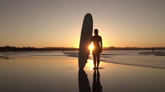 SLOW MOTION: Happy young female standing on sandy beach, holding longboard Stock Footage