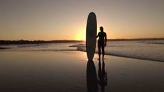 SLOW MOTION: Cheerful young female standing on sandy beach, holding longboard Stock Footage