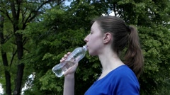 Young Girl in Blue Dress Drinks Water From the Bottle. Stock Footage