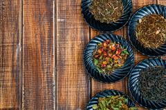 Different kinds of tea on plates on wooden background. Assortment of dry tea. Stock Photos