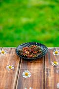 Dry rose tea on plate on wooden table with flowers of chamomile in garden and Stock Photos