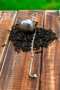 Vintage strainer with dry leaves of black tea on wooden background. Tea conce Kuvituskuvat