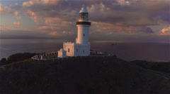 AERIAL: Flying around lighthouse on small hill above beautiful ocean lagoon Stock Footage