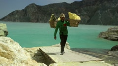 Worker carrying heavy basket of sulfur inside the crater of Kawah Ijen volcano Stock Footage