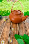 Brown teapoton on wooden with mint and chamomile table in garden and on natur - stock photo
