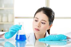 Asian female chemist exploring new medical frontiers - stock photo