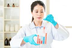 Asian female scientist researcher observing indicator color shift - stock photo