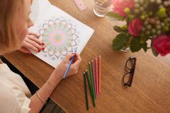 Female drawing in adult coloring book at home Stock Photos