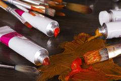Open tubes of brown paint and brushes Stock Photos