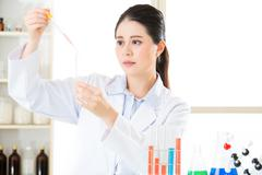 Careful, meticulous work of asian female scientist - stock photo