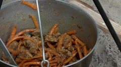 Carrots and Meat Cooking on the Fire in the Cauldron. Stock Footage