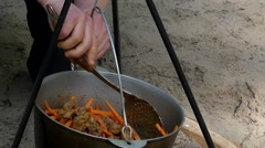 The Rice Cooking on the Fire. the Hands Prevents the Dish. Slow Motion. Stock Footage