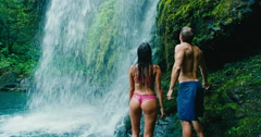 Couple Relaxing Under Waterfall Stock Footage