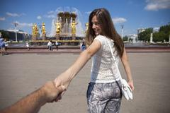 Follow me. Young happy girl pulls the guys hand Stock Photos