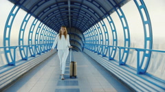 Young business woman with travel bag on wheels is on the transition from the Stock Footage