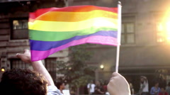 Wedding band on man's ring finger with flags waving in Gay Pride Parade in NYC Stock Footage