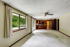 Empty room with carpet floor connected to kitchen with dark brown wooden cabi Stock Photos