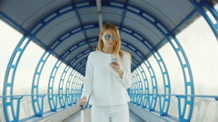 Stylish business woman in white suit goes through the tunnel, or the transition Stock Footage