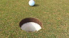 Slow motion golf ball into hole Stock Footage