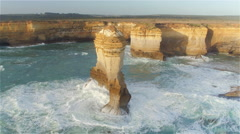 AERIAL: Flying around high limestone formation rising from shallow water - stock footage