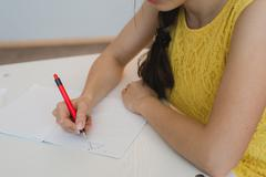 Close up of girl's hand with pen doing math, drawing triangle Stock Photos