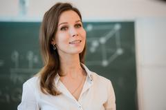 Happy teacher standing in front of black board Kuvituskuvat