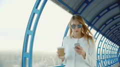 All business on the go. Business woman with a cup of coffee and the phone Stock Footage