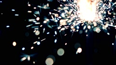 Blue and orange burning sparkler against dark background. Super slow motion Stock Footage