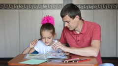 The girl first grader and Dad decide logical problems in the textbook Stock Footage