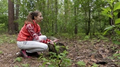 Young Beautiful Girl in the Forest Calls Squirrel. She Knocks a Nut on the Stock Footage