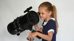 Seven-year girl looks in a reflector telescope Stock Footage