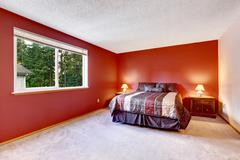 Red bedroom with beige carpet floor and bright colorful bedding. Two nightsta Stock Photos