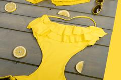 Yellow swimwear one-piece, swim shorts, aviator sunglasses, lemon on grey woo Stock Photos