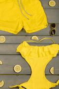 Yellow swimwear one-piece, swim shorts, aviator sunglasses, lemon on grey woo - stock photo
