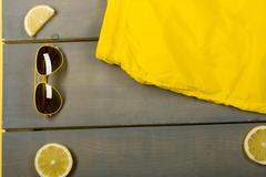 Man beach accessories on wooden background. Yellow Swim Trunks, aviator sungl Stock Photos