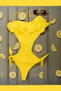 Yellow one-Piece swimsuit, aviator sunglasses between parts of lemons on grey - stock photo