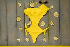 Woman beach accessories on wooden background. Yellow swimsuit one-piece, avia - stock photo