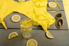 Yellow swimsuit one-piece, aviator sunglasses and lemonade  between parts of  Stock Photos