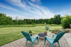 Beautiful house backyard with well kept lawn, trees. View from patio area Stock Photos