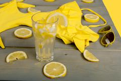 Lemonade, yellow swimsuit one-piece, aviator sunglasses between parts of lemo Stock Photos