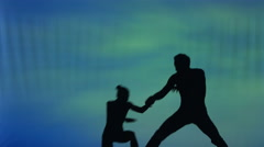 silhouette of a dancing couple, performing acrobatic stunts - stock footage