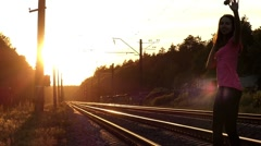 Slender Girl Walks on a Railroad at Sunset. Stock Footage
