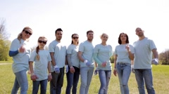 group of volunteers showing thumbs up in park - stock footage