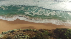AERIAL: Small ocean waves washing empty sandy shore below the high rocky cliff Stock Footage