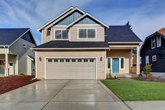 House exterior. American beige house with green grass. Garage with driveway Stock Photos